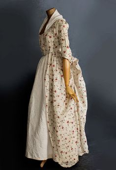 """1770s-80s. Made from sheer white cotton dimity printed with a repeat pattern of floral sprays. Referring to a gown made from similar fabric, the Victoria and Albert Museum wrote that """"the lack of decoration and use of cotton instead of silk indicates this gown was probably worn during summer afternoons for card games and tea parties, rather than for evening dress."""" The robe á l'anglaise style has a fitted bodice back and closed bodice fronts. The skirt, open in front, is pulled up ..."""
