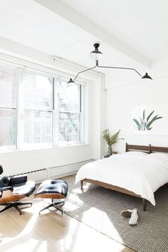 Gorgeous light, white and bright bedroom with midcentury accents and amazing black ceiling task lamp style pendant