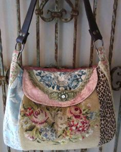 A dijon yellow, floral, vintage needlepoint is flanked by a french blue velvet chenille and a suede, leopard print fabric. The flap is a vintage