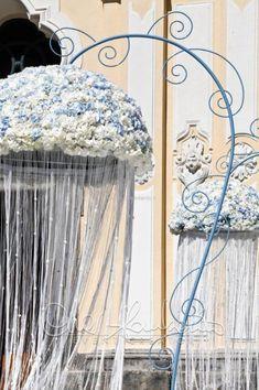 Imponenti meduse floreali per gli addobbi fuori la chiesa di un matrimonio dal tema marino.