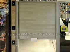 Защитные ролеты для дверей торговой секции. На большинство торговых защитных ролет устанавливаются электромехнические приводы и запорные устройства роллетного полотна. На фотографии виден более светлый электрический замок ролеты размещенный на её левой направляющей.