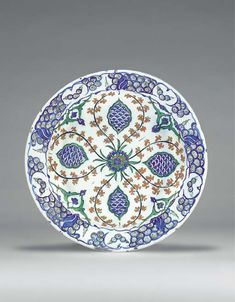 """AN IZNIK POTTERY DISH  OTTOMAN TURKEY, CIRCA 1575  With sloping rim on short foot, white interior painted in blue, green & black with red slip with a central blue & red flowerhead issuing red floral sprays forming a quatrefoil, each lobe containing a cusped ovoid cartouche with blue fish-scale, interstices with paired split-leaf panels, border with stylized wave & rock motif in blue & black, edge painted to imitate cusping, exterior with alternating paired tulip & flowerhead motifs12¼"""" diam."""