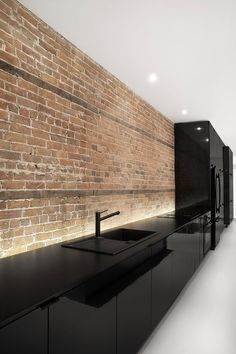 Brick wall splash back and black kitchen Espace St-Denis by Anne Sophie Goneau