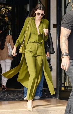 Kendall Jenner wears head-toe-toe olive green—a button-down shirt, long duster jacket, high-waisted trousers, matching bag, and nude heels
