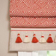 Roman shades: orange and natural white geometric with contrasting band and tassel fringe.