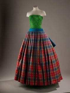Ball dress with a leaf green lace bodice, turquoise blue sash and bow, and tartan silk skirt: English, London, by Hardy Amies, 1989.