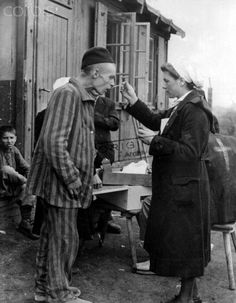 After the liberation of a concentration camp near Hannover on the 10th of April in 1945, a nurse of the Red Cross takes care of a survivor.