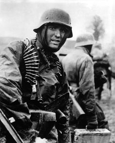 In a captured image distributed by the Signal Corps, a German trooper is seen near the Ardennes Forest. It is one of the most famous stills from the German side in World War II, and is one of several taken (along with newsreel film) on December 18, 1944 near Poteau, Belgium during the Battle of the Bulge. The soldier is part of the 1st SS Panzer Division, Kampfgruppe Hansen, and he is draped in a 7.92mm MG42 ammunition belt. He has been wrongly identified as Walter Armbrusch.