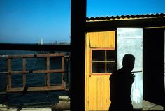 Alex Webb AZERBAIJAN. Baku. 2001.The man made island of Neft Baslani (Oily Rocks). Worker outside hut.