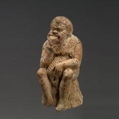 Greek terracotta statuette of a seated Actor, Attic, middle of the 4th century B.C. He assumes a thinking position, his right hand, placed on his chin, supports the head in an attitude of reflection, as if he is planning a prank. This genre of person is used in ancient low comedy to designate a slave; he was a precursor of the cunning, skilled slave, who would become a very important character in the New Comedy, 8.9 cm high. Private collection