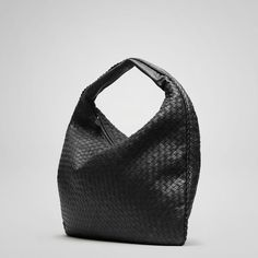 """Bottega Veneta Nero Intrecciato Nappa Maxi Veneta style 181140 V0016 8175 Inspired by the shape of the timeless hobo, the traditional Veneta is a signature element of Bottega Veneta's handbag collection. Its concave armhole and flattened, minimalist body are balanced by a substantial handle, making it both roomy, comfortable as well as distinctive. An ideal bag for daily use. With gunmetal hardware. Lining:Suede Dimensions:21.7"""" W x 9.8"""" H x 1.2"""" D"""