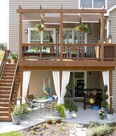 Two tiers of function: How to make the most of the space below a deck with seating, a hanging chair and curtains that close for privacy. More beautiful backyards: http://www.midwestliving.com/garden/ideas/30-beautiful-backyards/
