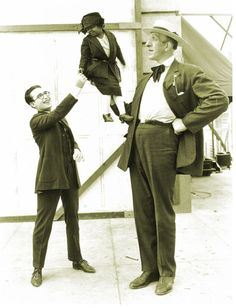 Harold Lloyd shakes hands with a little person.
