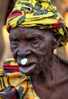This woman from the ethnic group of the Lobi people in Burkina Faso is over 90 years old and is wearing a small white lip disk.  The Lobi people are perhaps the shiest people of Burkina Faso. Men still carry bows and arrows, and old women wear lip disks. Spread throughout Burkina Faso, Ghana and Ivory Coast, the Lobi also have the most characteristic villages; thanks in part to their shyness they have maintained their traditions intact.   Blog: Dietmar Temps, travel blog  Website, gallery…