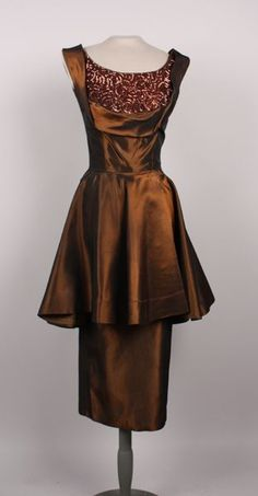 Cocktail dress by Emma Domb, 1957-1959; copper acetate with double skirt and sequined bodice. Scoop neck, with deep V-neck in back. Wide shoulder straps.