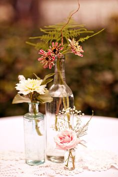 use differently sized glass bottles and only one or two flowers per