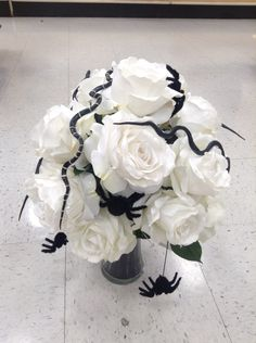 Halloween floral arrangement of white roses in a vase with black sand covered in snakes and spiders.