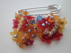 Brooch Cascade in orange, red and blue's £14.50