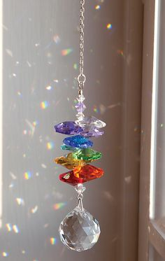 """Austrian Crystal Rainbow Maker  Hang it in a sunlit window, give it a tap, and send rainbow-hued prisms dancing around the room. Clear and colored crystals hang from a steel chain. 3"""" long, 9"""" with chain."""