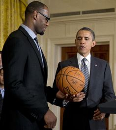 President Barack Obama accepts a signed basketball from Miami Heat forward LeBron James as he welcomes the NBA basketball world champions to the White House.