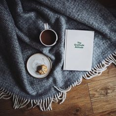 Cup of tea with a journal and a cake on a blanket