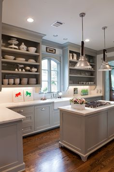 kitchen with cooktop in island.  no hood.  like the white counter with pale grey cabinets.  little too ornate ye olde style for me but like the color combo