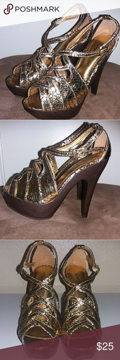 Metallic Gold Heels These heel are manmade material and also made in China.Wooden heel.  Medium fit. Never worn them. Still in good condition. Qupid Shoes Heels