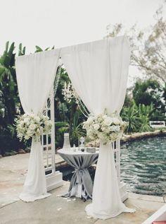 arche mariage avec voilage blanc, cérémonie de mariage laïque au bord d'ne piscine
