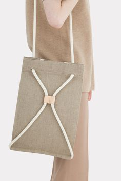 Pocket bag can be worn as a sack or as a shoulder bag. To transform it, simply pull the string. It features a 100% linen lininig and one interior pocket.