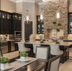 Greige color wall, love the lights above the island. I would love that stone. Looks nice with dark wood cabinets