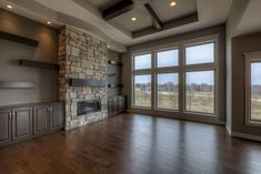 Great room with ceiling high stone fireplace, built-in cabinets and shelving, ceiling detail. Huge windows.