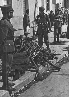A German fallschirmjäger looks at a pile of captured weapons; in the background captured Greece officers are lined up in Corinth, 1941