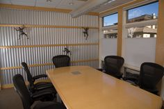 Industrial office, corrugated metal      Walls of corrugated metal line Michael Doty & Associate's conference room, adorned with climbing metal figures.