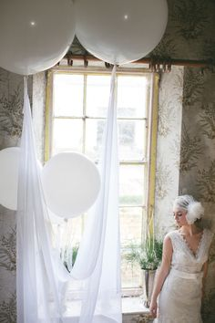 line of balloons along front windows( w/ draped tulle or simple ribbon) to fill up space and create canopy above. wrap in tulle and insert led light. http://www.koyalwholesale.com/c1422/big-balloons-new.html or http://www.balloonsfast.com/36inchlatexballoons.html