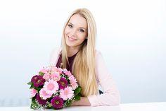 Портрет улыбающегося молодой женщины, держащей букет цветов