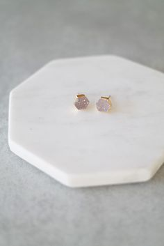 """Glam up your ears with these hexagonal Druzy stones set in gold. Details: - 1/3"""" wide - Comes in pink-purple, blue, and grey."""