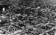 Vista aérea da cidade, a partir da Praça da Saudade, no canto inferior esquerdo. Um pouco mais acima, a Praça do Congresso e, mais à frente, o imponente Teatro Amazonas. Acervo: Biblioteca Samuel Benchimol.