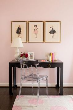 Pink and black kid's bedroom features a three vintage fashion prints lining pink walls over a black desk accented with gold ring pulls, Bungalow 5 Jacqui Desk, topped with a white double gourd lamp with lucite base paired with a lucite chair atop a gray and pink rug, Genevieve Gorder For Capel, Pink Dot Rug.