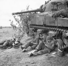 A Sherman tank crew of 'C' Squadron, 13th/18th Royal Hussars rest and write letters home by the side of their vehicle, Normandy, 10 June 1944.