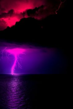Lightning and water tornado over ocean, purple under dark clouds, red glow above