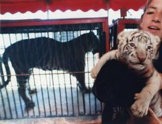 """""""Kathleen Umstead, wild animal trainer with Clyde Beatty-Cole Brothers Circus holds a three-week-old white Bengal tiger with black stripes Wednesday as the circus pulled into Newnan for four shows. In the background is one of the many other tigers in the show. The baby tiger's name is 'Akbar' and was born in Mobile, Alabama."""" AJCP1673b, Atlanta Journal Constitution Photographic Archives. Special Collections and Archives, Georgia State University Library."""