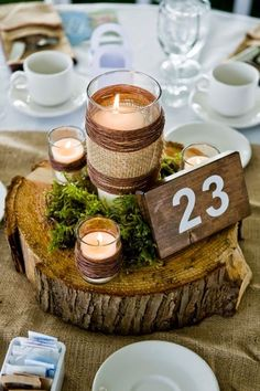 rustic wedding table numbers, tree trunk, burlap, candles DIY wedding planner with ideas and tips including DIY wedding decor and flowers. Simple Wedding Centerpieces, Rustic Wedding Centerpieces, Wedding Table Numbers, Mason Jar Centerpieces, Centerpiece Ideas, Flowerless Centerpieces, Moss Wedding Decor, Rustic Table Centerpieces, Burlap Wedding Decorations