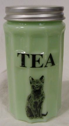 Jade Glass Jadite Canister TEA Sitting Cat Design * Caz Metal Tops . $32.00. Sharp lined sides.  The flat frontace that holds the canisters ingredient label.  This is cast in a green milk glass. Also known as Jade or Jadiete.  Each piece has the  decals hand fired in Western Pennsylvania.   The measurements of seven and a half inches by four inches are set by the depression glassware that would fit into classic cabinets.  This is part of an entire set that melds together in ...