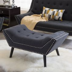 Rife with button tufting and silver nail head detail, our Tamblin Designer Ottoman dares to be different. This style-conscious living room furniture is built with an MDF frame, firm fire retardant foam cushioning, and black solid birch legs.