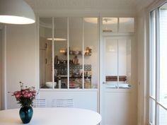 En lieu et place d'une cloison classique, les designers de la Manufacture nouvelle ont installé une verrière intérieure en bois, équipée d'une porte. La petite cuisine de cet appartement haussmannien est ainsi séparée du salon, tout en conservant une perspective et une luminosité idéale. Le chantier étape par étape.