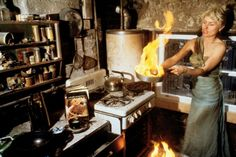 """Debbie Harry cooking, 1977, by Chris Stein  The Guardian has the story of the shot:     One shot, of her """"cooking"""" (that is, brandishing a flaming frying pan in a blackened kitchen), has a wild humour that's typical of Stein's sensibility – it's one that the writer Glenn O'Brien identifies in an essay in the book as """"the light side of the dark side"""". The photoshoot happened when the couple returned from a tour in 1977 to discover their apartment had burned down, after an electrical fire. ..."""