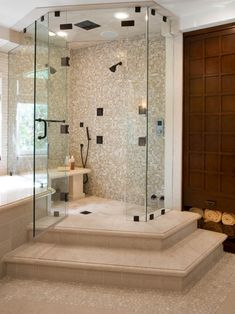 this beautiful shower combines mosaic pebble and standard tile for a luxury feel a glass door and shower stairs make this bathroom feel especially