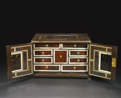 An Indo-Portuguese tortoiseshell and ivory table cabinet part late 17th century in a mahogany and tortoiseshell veneered case with a fitted interior of eight small drawers arranged around a central square drawer, adapted in the late 18th or early 19th century