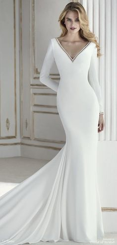 This dress demonstrates that simplicity is synonymous with beauty, femininity and elegance. A wonderful mermaid wedding dress in crepe with a train. A long sleeve design that contrasts the minimalism of the design with two deep Vs on the front and back, edged with beaded appliqués, for a very sensual look. A design that will draw everyone's gaze. #weddingdress