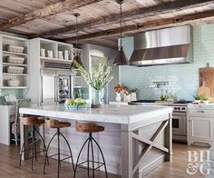 A rustic kitchen wouldn't be complete without a wood-beam ceiling and open shelving. Seafoam-color subway tile is the perfect subtle pop of color for this decorating style. The ceiling-high backsplash makes a bold statement in an otherwise understated room.